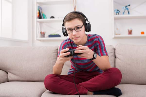 Boy playing video game on couch.