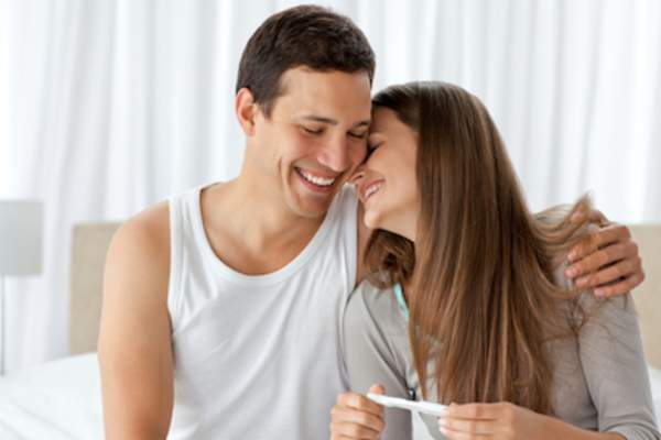 Young couple happy with pregnancy test.