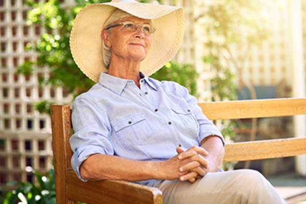 Senior woman relaxing outside while wearing a wide-brimmed hat.