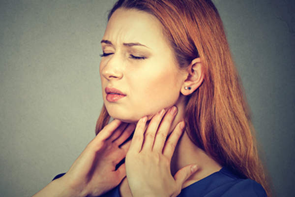 Woman grimacing with throat, thyroid, or neck pain.