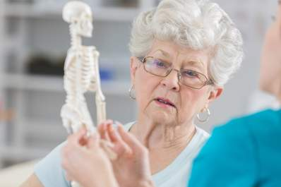 Senior woman with osteoporosis looking at skeleton model.