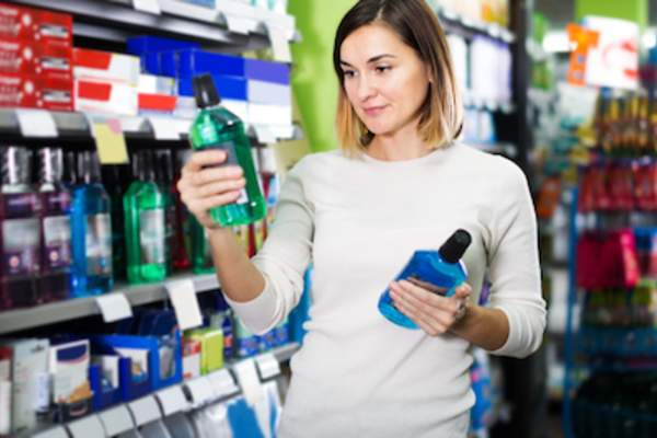 Woman comparing mouthwashes at the supermarket.