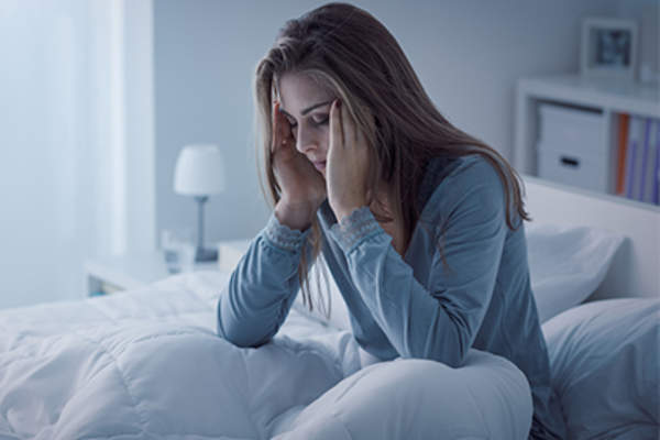 Young woman sitting up in bed feeling sick.