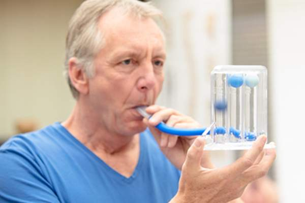 Man with COPD measuring his lung function.