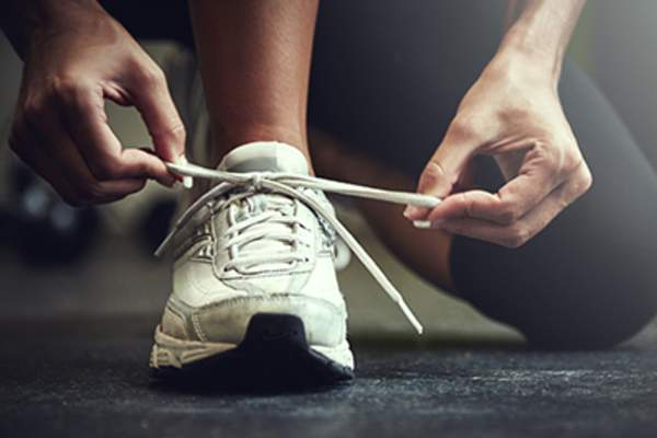 Person tying shoelaces on sneakers.
