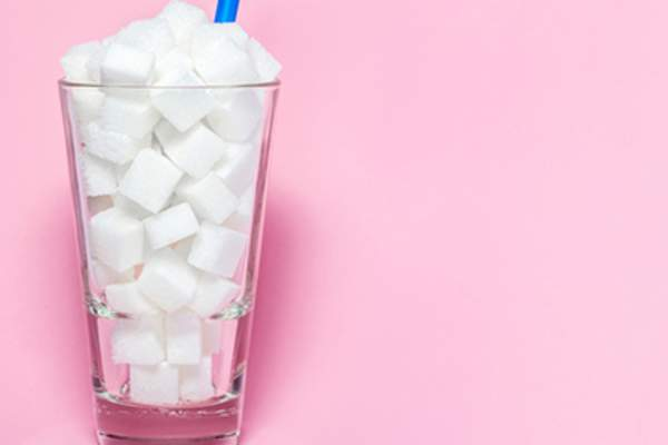 Glass of sugar cubes, unhealthy drink concept.
