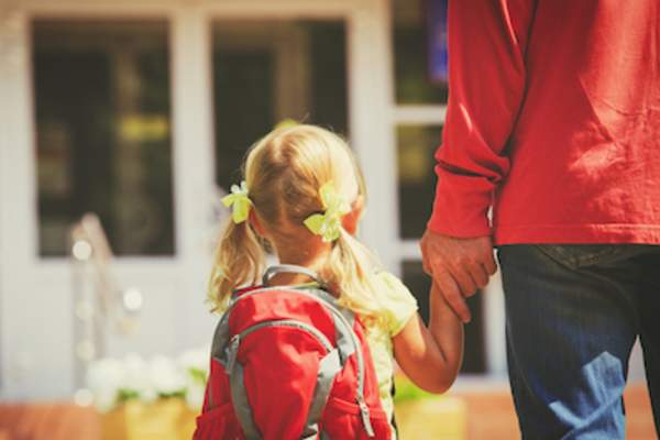 Little girl with pigtails and red backpack holds her parent's hand.