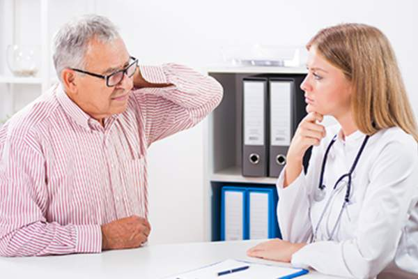 Patient with neck pain talking to a doctor.