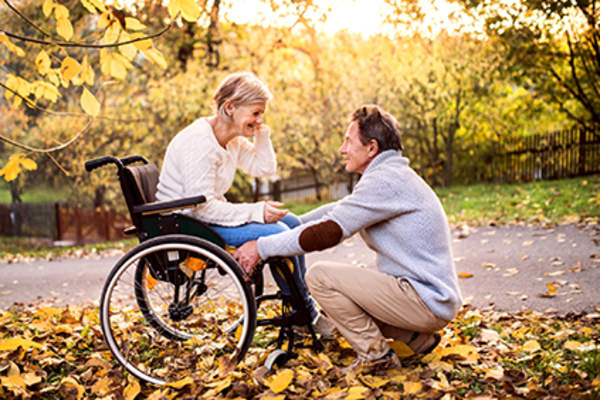 Woman in a wheelchair with her husband in the fall.