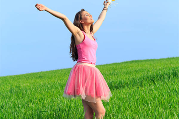 Happy young woman in pink dress outside on warm, sunny day.