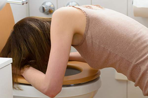 Young woman with morning sickness vomiting.