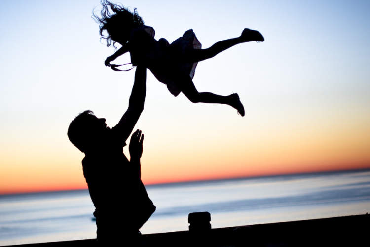 silhouette of father playing with daughter