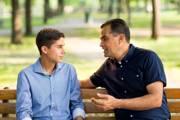 Father and son talking on a bench outdoors