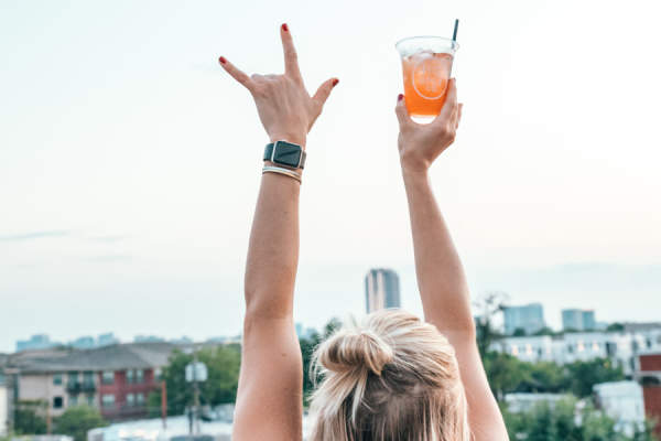 woman with arms in air holding cocktail