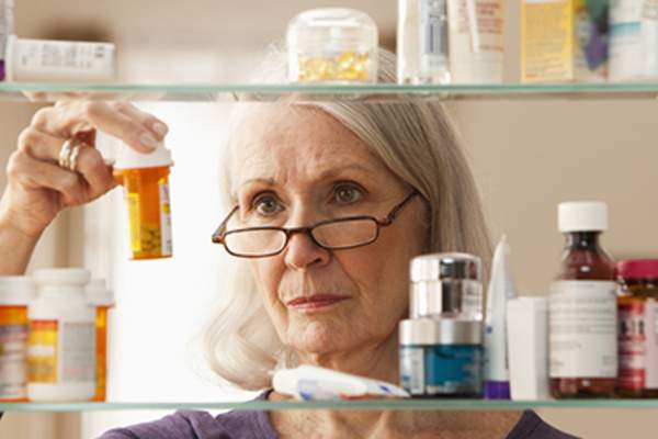 Senior woman looking at meds in medicine cabinet.