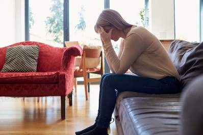 Depressed mature woman sitting on sofa at home.