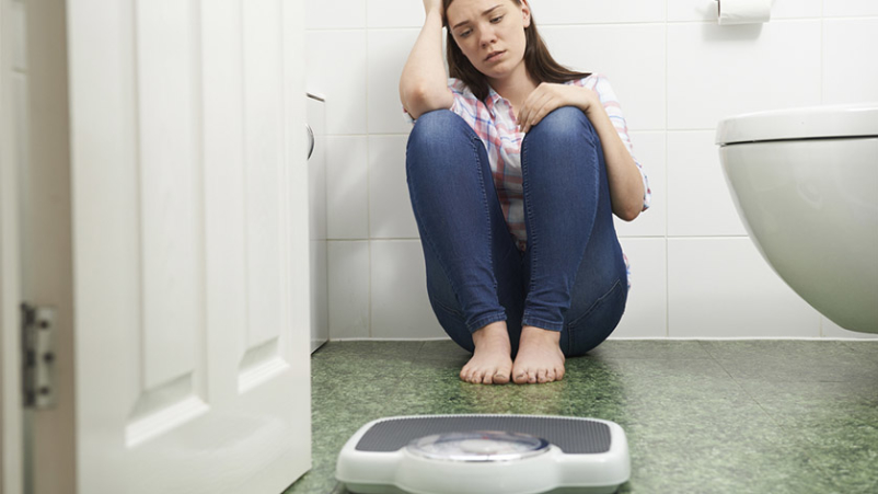 Teen girl with eating disorder sitting on bathroom floor with scale.