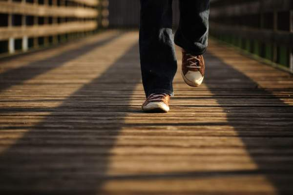 close up of shoes walking on boardwalk