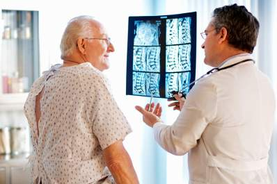 Senior man with bone loss talking to doctor about x-rays.