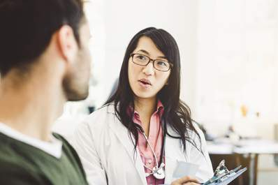 Woman doctor talking to young man image.
