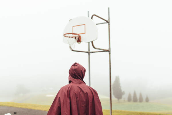 Person in raincoat standing in front of basketball hoop