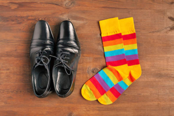 Black dress shoes and colorful socks on wood floor.