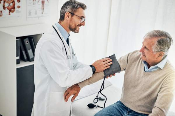 doctor testing patient's blood pressure