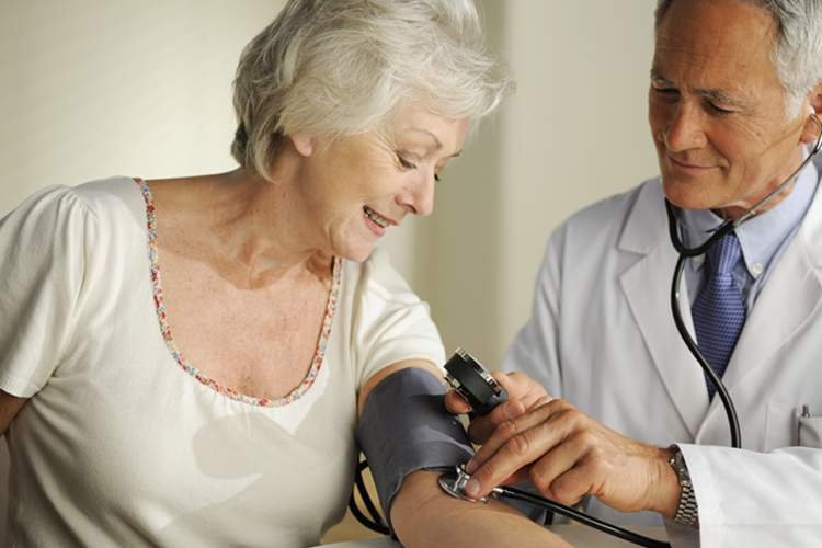 Doctor measuring a senior women's blood pressure.