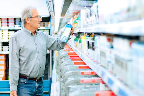 Man shopping for milk check label for fat content.