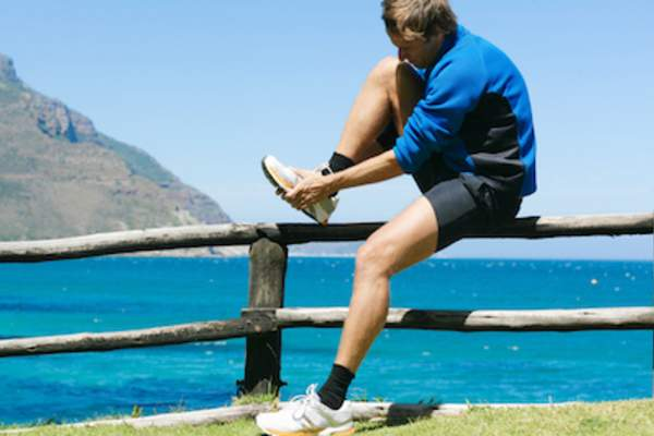 Man stopping his jog to rub foot from gout flare-up.