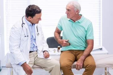 Man discussing stomach pain with his doctor.