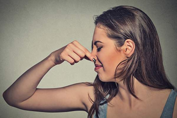 Woman pinching her nose because of a bad smell.