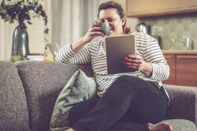 Overweight woman looking at tablet drinking tea on the couch at home.