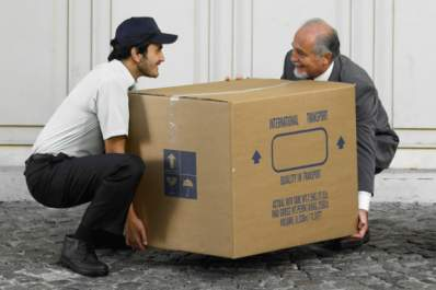 Two men strain their backs lifting a large box.