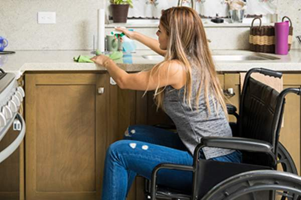 Woman in a wheelchair washing dishes.