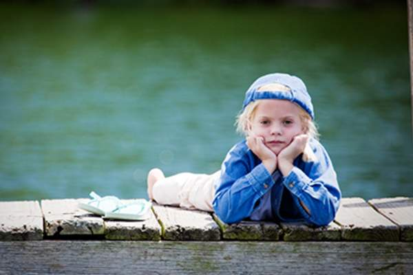 Unhappy child lying on a dock on a lake.