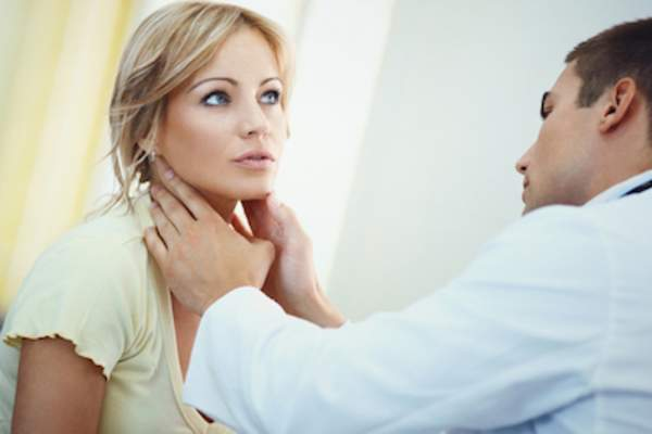 Doctor examining patients thyroid.