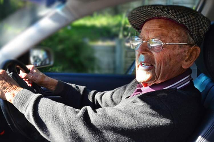 Elderly man driving a car.