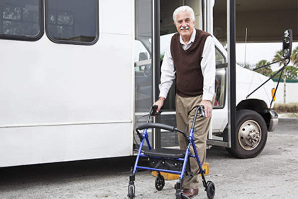Man with walker leaving senior transport van.