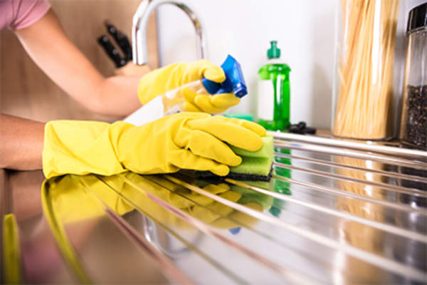 Cleaning kitchen sink wearing rubber gloves.