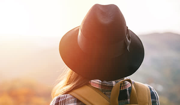 Woman hiking at sunset wearing hat.