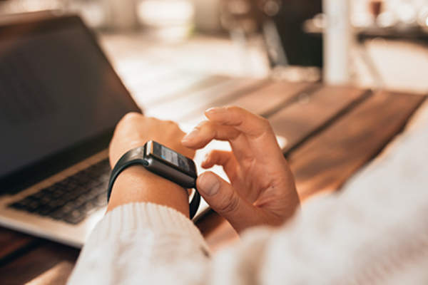 Woman using smartwatch at work on laptop.