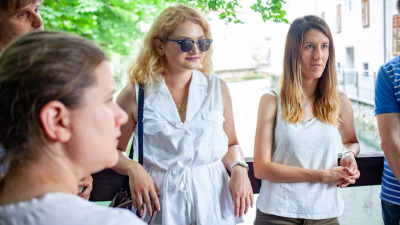 Group of people talking, one lady wearing sunglasses.