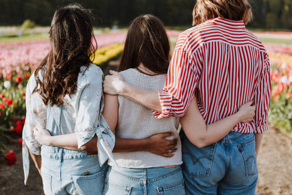 three young women with arms wrapped around each other