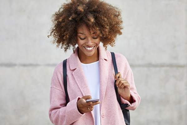 Smiling woman looking at a period tracking app.