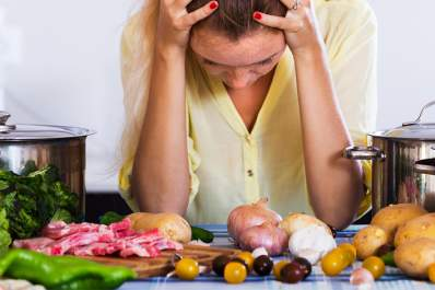 Woman with headache in kitchen, food on counter.