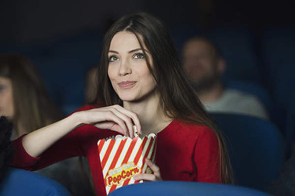 Woman at the movies eating popcorn.