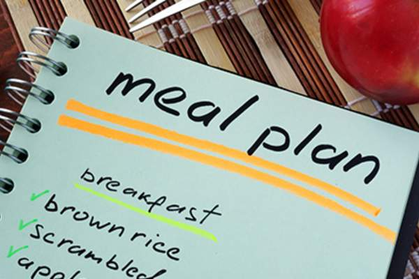 Notepad with meal plan and apple.