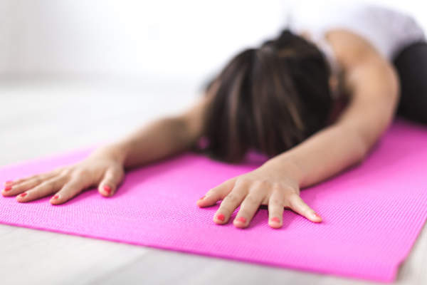 woman doing yoga indoors on pink mat