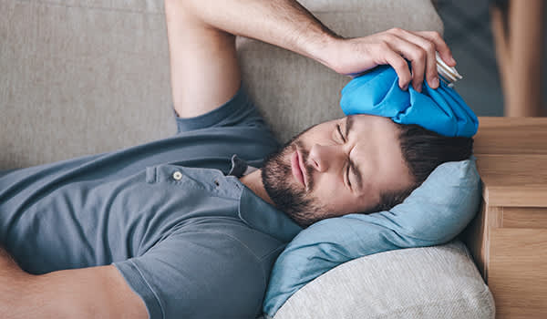 Man lying down on couch with headache holding ice pack on his head.